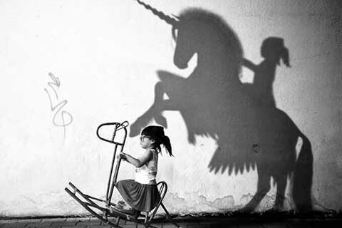 Little Girl on rocking horse dreaming of being a magical Horse or Unicorn rider